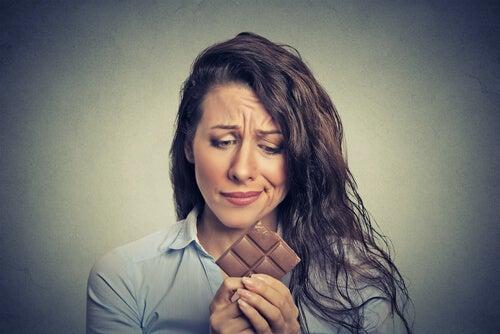 Mujer con tableta de chocolate en las manos deseando comérsela
