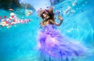 Mujer debajo del agua rodeada de pétalos