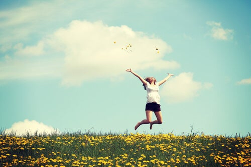 Mujer feliz en el campo saltando