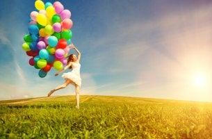 Mujer feliz con globos de colores en el campo