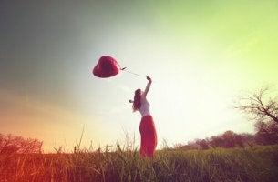 Mujer con globo de corazón disfrutando de la vida al aire libre