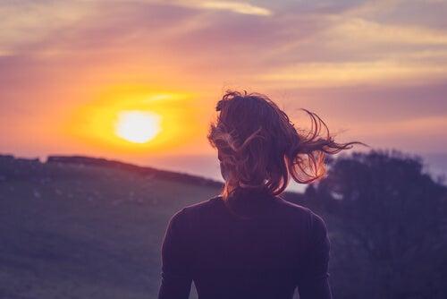 Mujer mirando el atardecer en la montaña