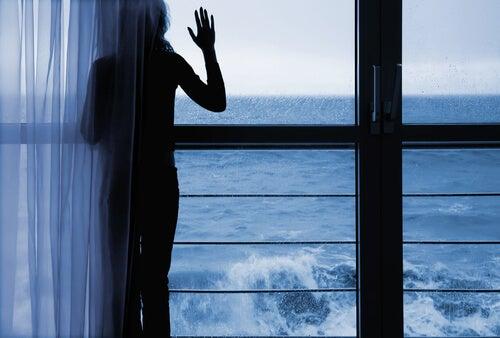 Mujer preocupada mirando por la ventana el mar