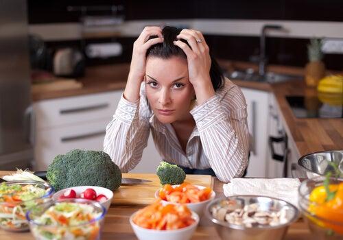 Mujer nerviosa con mucha comida en la mesa