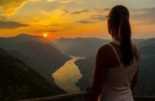 Mujer observando el atardecer desde la montaña
