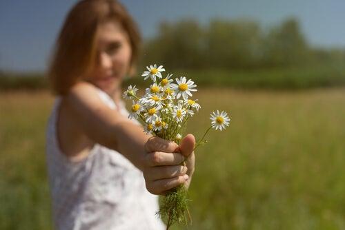Mujer complaciente ofreciendo flores