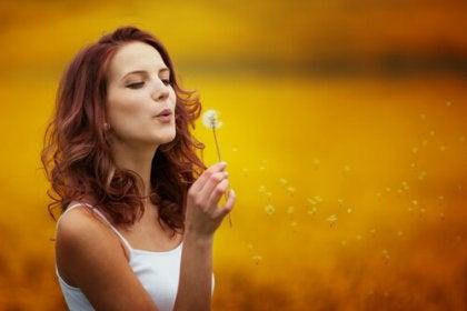 Mujer que sopla una flor con optimismo