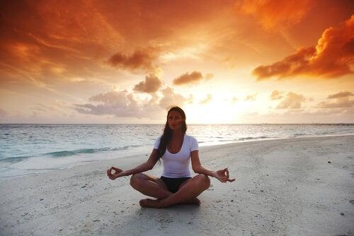 Mujer en posición de loto en la playa haciendo meditación