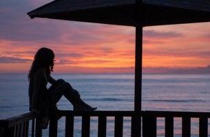 Mujer sentada en el balcón y observando el horizonte con nostalgia