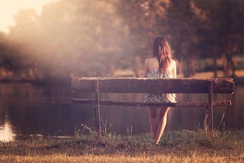 Mujer pensado sentada en un banco