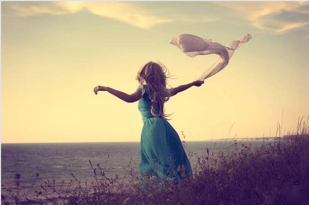 Mujer sola mirando el horizonte con un pañuelo en la mano
