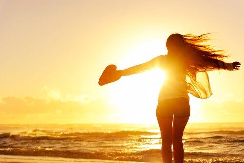 Mujer sola en la playa con un corazón en la mano
