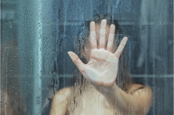 Mujer sola detrás de la ventana duchandose