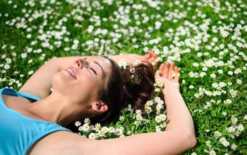 Mujer tumbada en el campo con margaritas