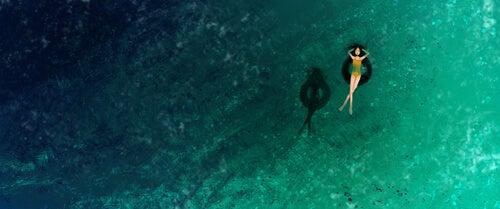 Mujer tumbada en el flotador en el mar