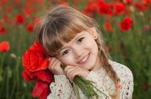 Niña sonriendo con ramo de flores rojas