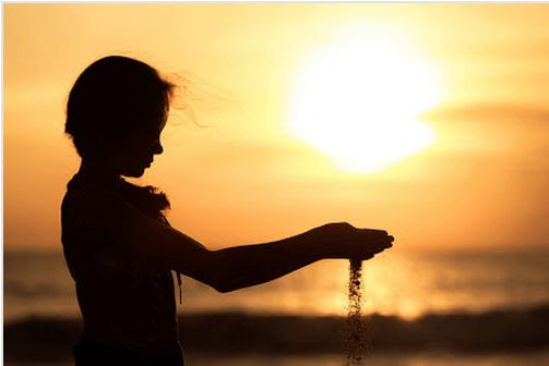 Niño con arena en las manos dejándola caer como símbolo del perdón