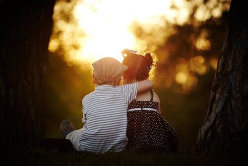 Niño sentado abrazando a niña al atardecer