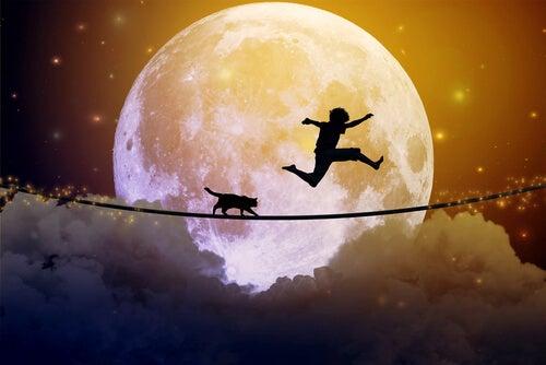 Niño sobre una cuerda al lado de la luna