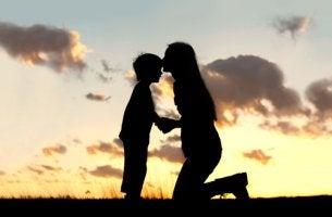 Madre dándole un beso a su hijo para fortalecer su autoestima