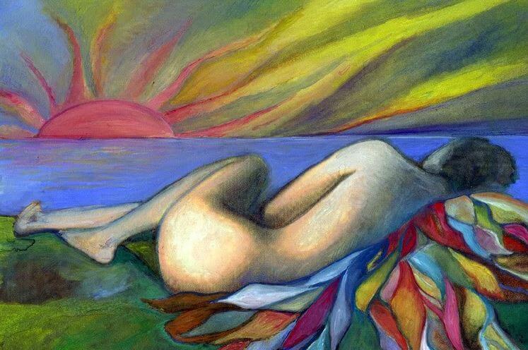 Mujer tumbada mirando el atardecer en la playa