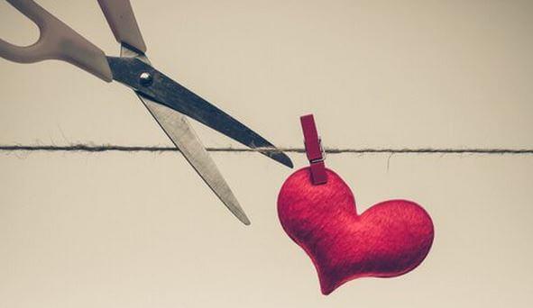 Corazón colgado de una cuerda mientras una tijera intenta cortarla