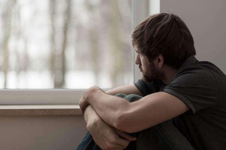 Hombre mirando por una ventana con fatiga emocional