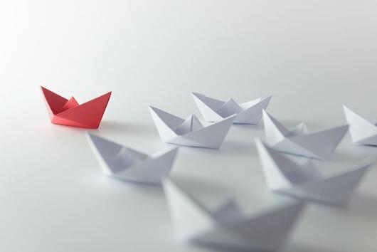 Barco de papel rojo seguido por barcos de color blancos