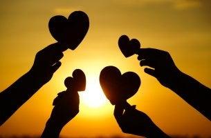 Manos sosteniendo corazones representando actos de bondad