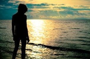 Mujer cabizbaja delante del mar