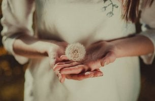 Mujer con un diente de león en sus manos como símbolo de humildad