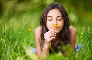Mujer oliendo una flor con cara de felicidad