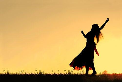 Mujer dando las gracias al amanecer
