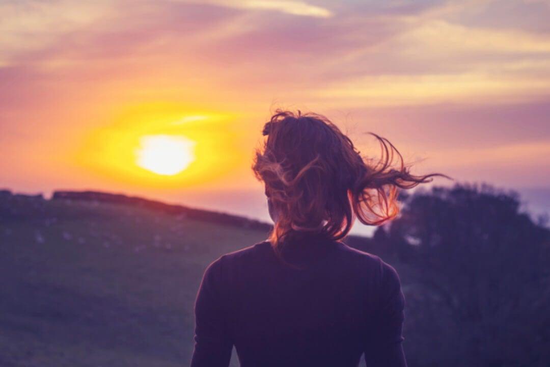 Mujer mirando el sol ponerse