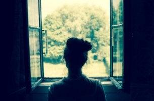 Mujer mirando por la ventana y recordando