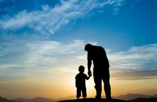 Padre enseñando a su hijo el atardecer