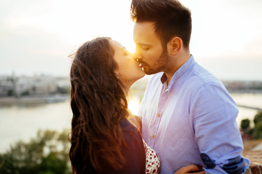 Pareja dándose un beso representando ser más románticos