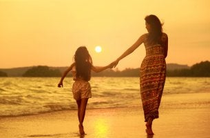 Madre e hija caminando por la playa