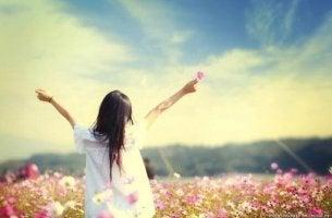 Mujer con una flor en la mano mirando al infinito