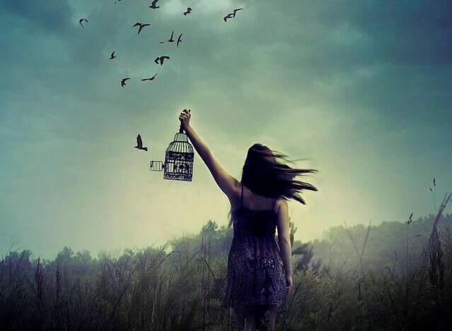Mujer dejando ir a los pájaros de su jaula