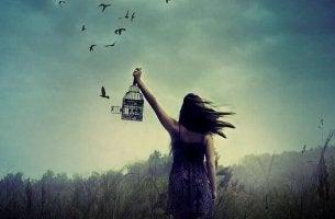Mujer dejando libres a los pájaros en su jaula