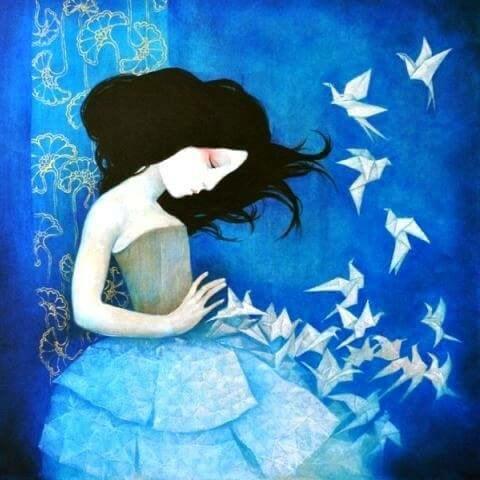 Mujer triste con pájaros de papel