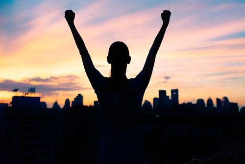 Persona de éxito levantando las manos
