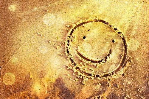 Cara dibujada en la arena feliz de su buena suerte