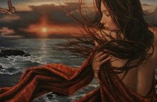 Mujer abrazándose frente al mar