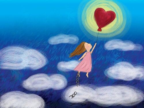 Niña volando con un globo de corazón en la mano