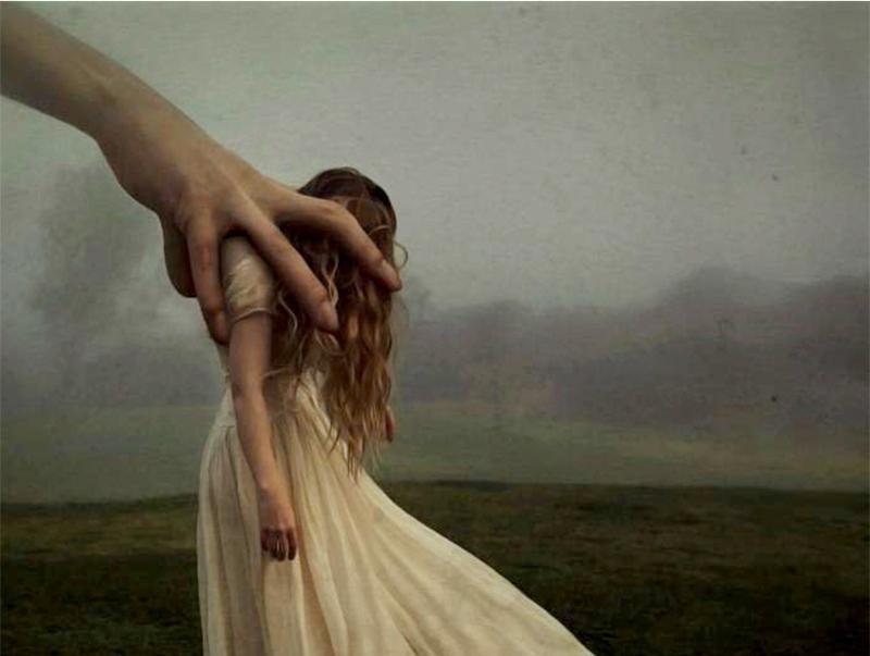 Mujer sujetada por una mano