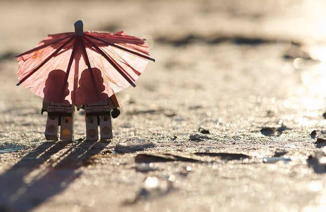 Dos muñecos bajo un paraguas