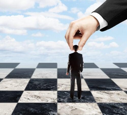 Hombres sufriendo la manipulación de otro como si fuera un peón de ajedrez