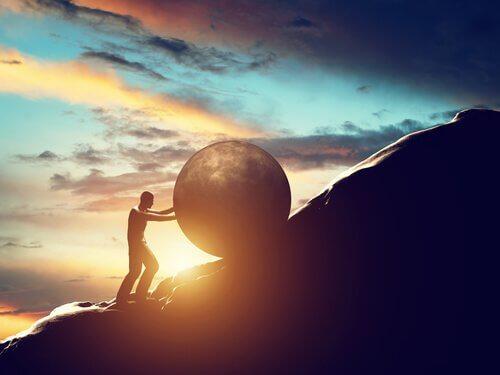 Hombre subiendo una cuesta de una montaña con una piedra